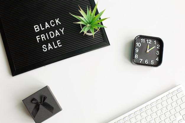 Текст черная пятница распродажа на черной доске для писем с компьютерной клавиатурой, подарочной коробкой и будильником