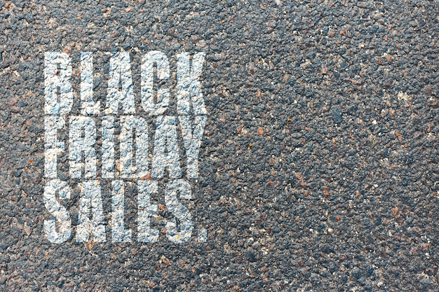 Text of black friday sales, on the background of asphalt.