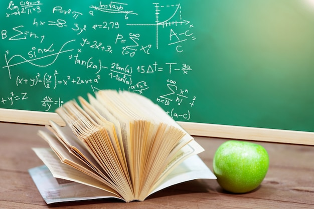 Text book and green apple on desk with green board