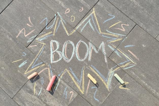 Text boom drawing crayons on gray asphalt