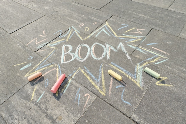 Text boom drawing with crayons on gray asphalt