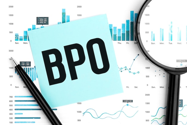 Text bpo business process outsourcing on blue sticker, magnifier, pen, graphs. business flat lay.