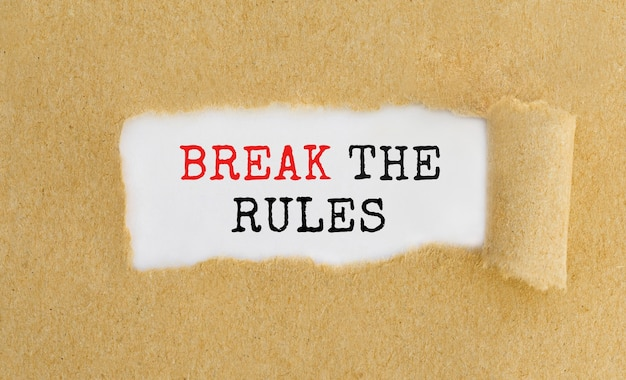 Text break the rules appearing behind ripped brown paper.