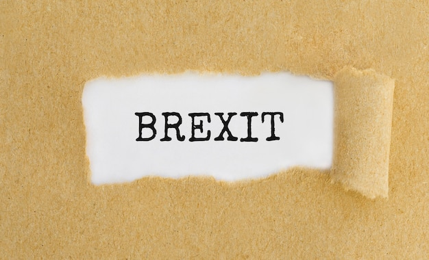 Text brexit appearing behind ripped brown paper