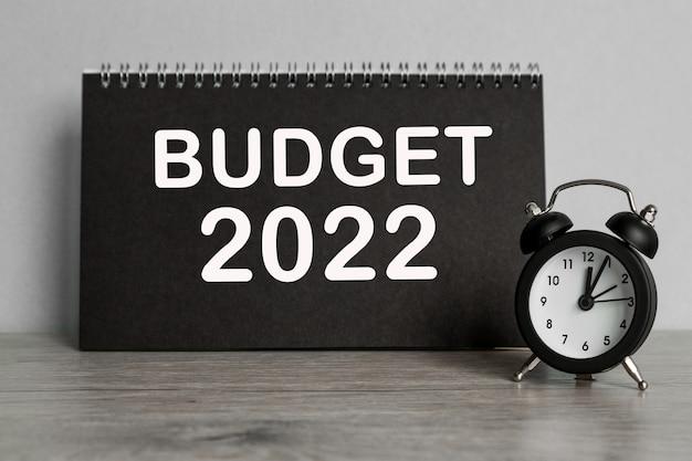 텍스트 예산 2022 . 검은색 노트북과 책상 배경의 시계.