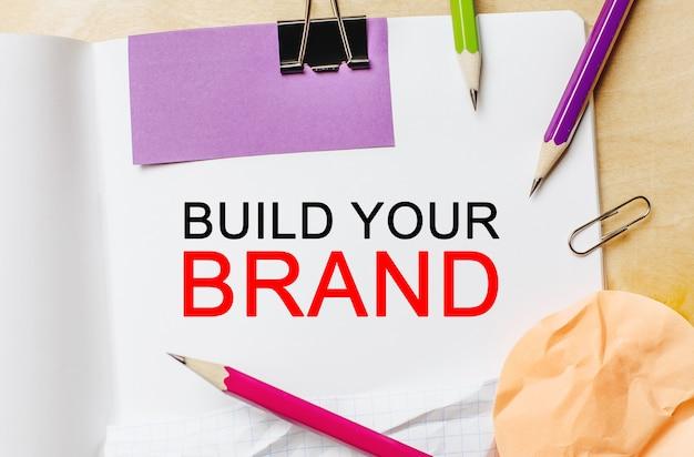 Текст создайте свой бренд на белом фоне для заметок с карандашами, наклейками и скрепками