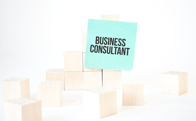 Text business consultant writing in green card cube ladder. white background.