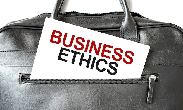 Text business ethics writing on white paper shit in the black business bag. business concept