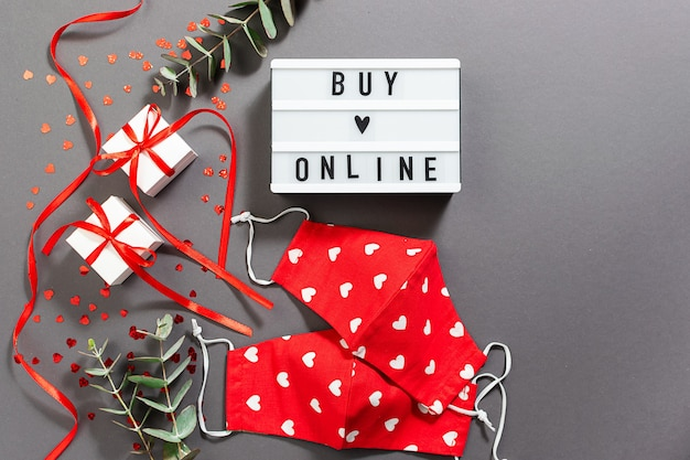 Text buy online on the lightbox with gift boxes, eucalyptus twigs and lap top on gray table.