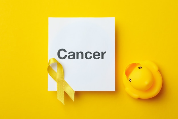 Text cancer, awareness ribbon and rubber duck on yellow