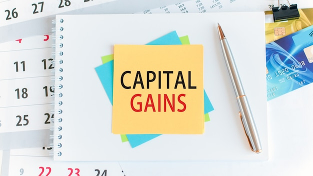 Text capital gains written on yellow paper square shape. credit cards, pen, stationery on the white desktop background. business, finance and education concept. selective focus.