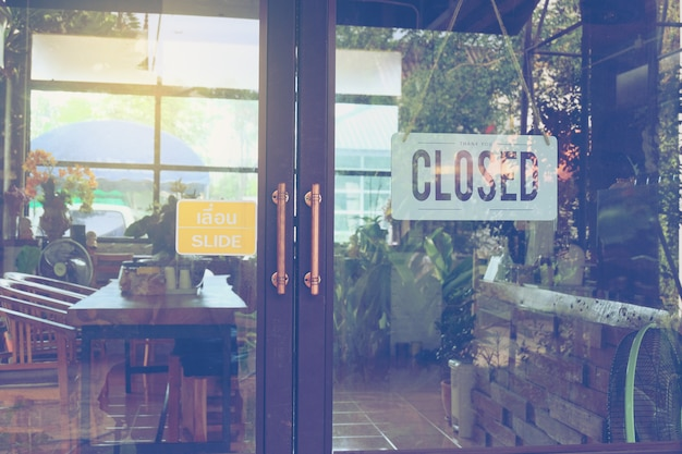 Text closed on door sign and hanging up on glass door of coffee shop