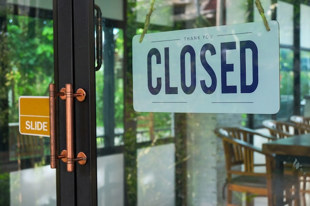 Text closed door sign and hanging up on glass door of coffee shop .