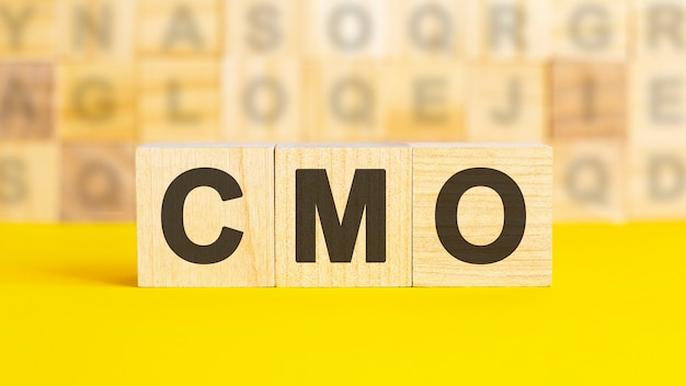 The text cmo is written on wooden cubes on a bright yellow surface. in the background are rows of cubes with different letters. business concept. cmo - short for chief marketing officer