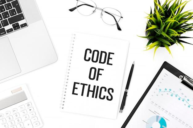 ノートブックに倫理規定をテキストで送信します。ノートパソコン、電卓、チャート用クリップボード、メガネ、ペン、オフィスの机の上の植物。フラットレイ、上面図。ビジネスコンセプト。