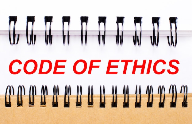 白と茶色のスパイラルメモ帳の間の白い紙に倫理規定をテキストで記入します。