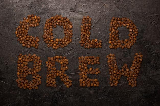暗いコンクリートの背景にコーヒー豆からレイアウトされたテキストコールドブリュー