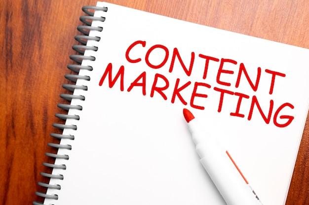 Текстовый контент-маркетинг, написанный в блокноте, офисный деревянный стол и красный маркер сверху, концептуальное изображение для заголовка блога или изображения заголовка. выдержанный винтажный цвет.