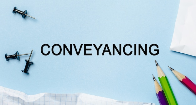Text conveyancing on a white notepad with pencils on a blue background. business concept