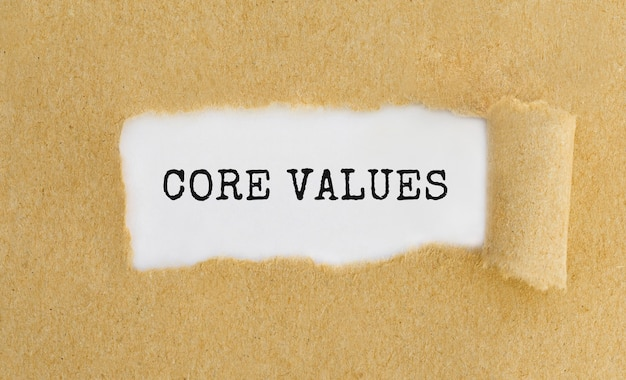 Text core values appearing behind ripped brown paper.