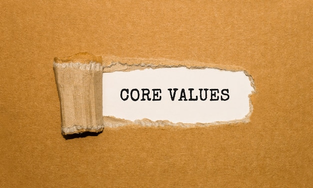 The text core values appearing behind torn brown paper