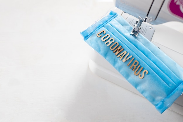 파란색 수제 의료 마스크에 coronavirus라고 문자하세요. 마스크는 spunbond, sms, meltblown으로부터 집에서 손으로 꿰매어 보호합니다. 소프트 포커스입니다.