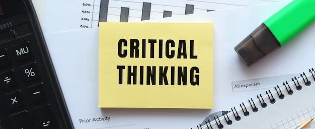 Text critical thinking on the page of a notepad lying on financial charts on the office desk