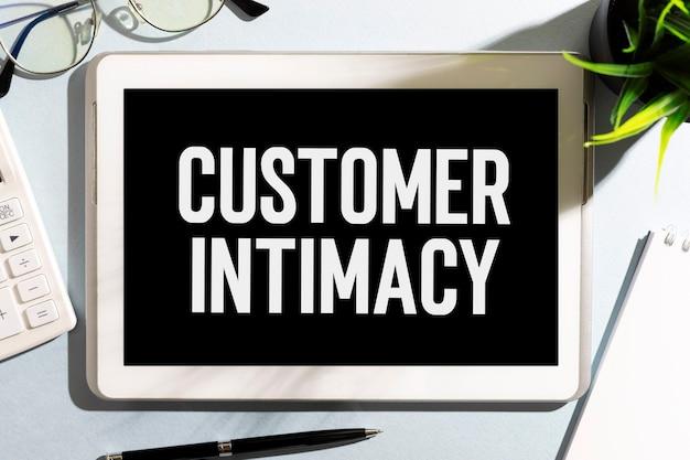 テーブル、電卓にcustonerintimacyとテキストを送信します。ビジネスコンセプト。フラットレイ。