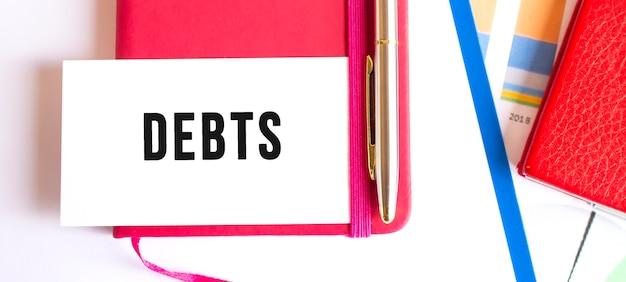 사무실 책상에 메모장에 누워 흰색 카드에 텍스트 debts. 금융 개념.