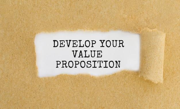 찢어진 갈색 종이 뒤에 나타나는 텍스트 develop your value proposition