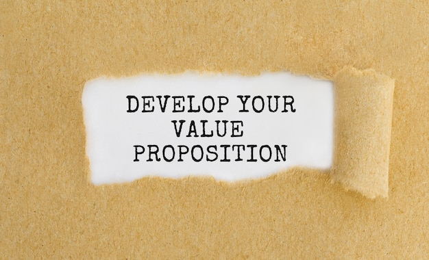 Text develop your value proposition appearing behind ripped brown paper