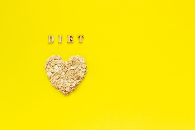 Text diet and oat flakes in shape heart on yellow background.
