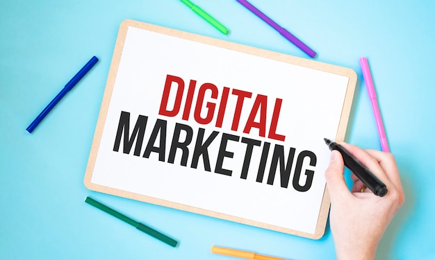 Text digital marketing on a notebook surrounded by colored felt-tip pens, business concept idea,