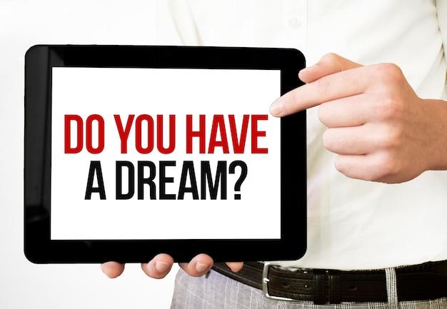 テキストあなたは白い背景の上のビジネスマンの手でタブレットディスプレイに夢を持っていますか。