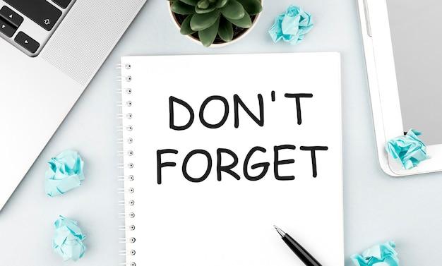 ノートブックにテキストを忘れないでください。ノートパソコン、紙片、ペン、オフィスの机の上の植物。フラットレイ、上面図。計画コンセプト。