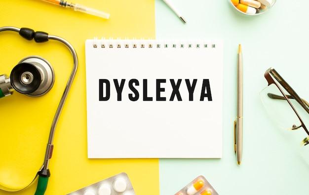 Текст dyslexya на блокноте со стетоскопом и ручкой на желтом фоне. медицинская концепция.