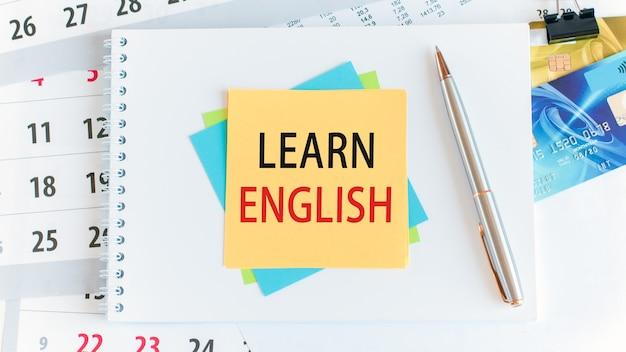 黄色い紙の正方形に書かれたテキストは英語を稼ぎます。白いデスクトップ上のクレジットカード、ペン、文房具。ビジネス、金融、教育の概念。セレクティブフォーカス。