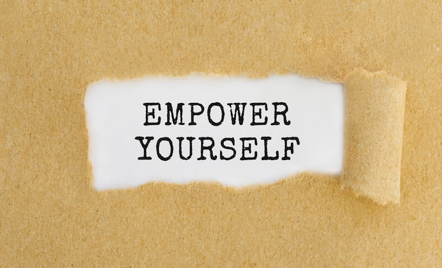 Text empower yourself appearing behind ripped brown paper