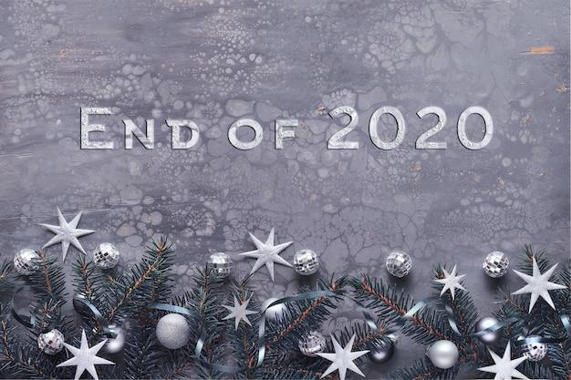 Текст конец 2020 года. новогодний фон, плоская планировка, еловые веточки, украшенные игрушками, зеркальные диско-шары