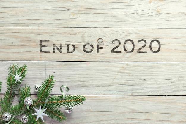 Текст конец 2020 года. квартира с угловыми украшенными еловыми ветками и игрушками из белого и серого серебра.