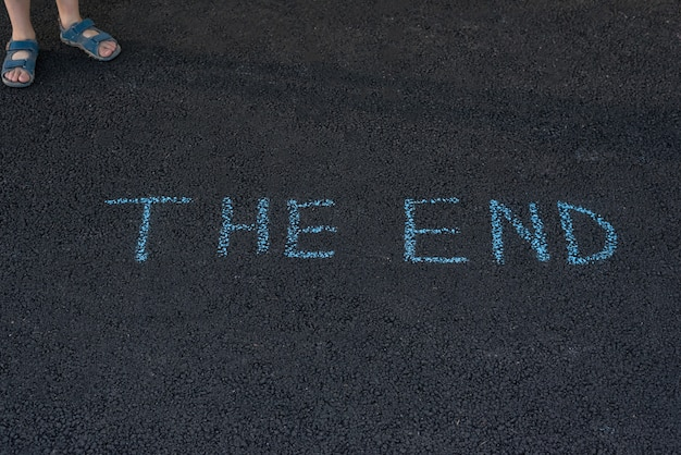 Text the end underfoot. feet and inscription on asphalt. notice on road.
