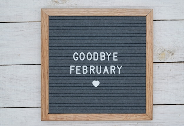 Text in english goodbye february and a heart sign on a gray felt board in a wooden frame.