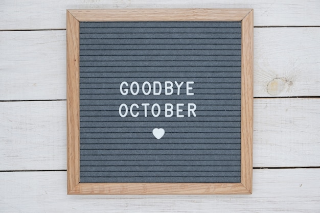 Text in english goodbye october and a heart sign on a gray felt board in a wooden frame.
