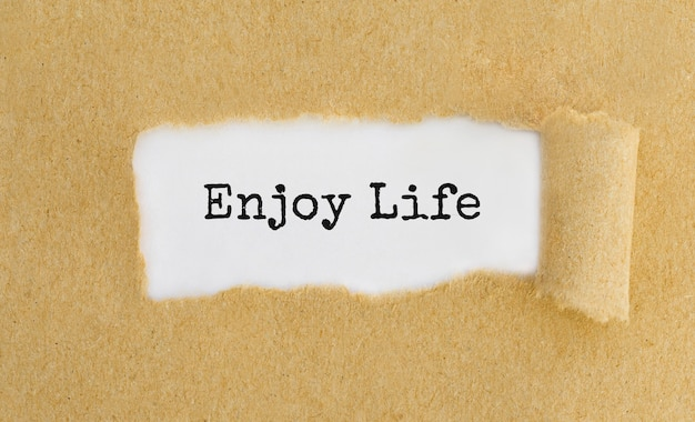 Text enjoy life appearing behind ripped brown paper.