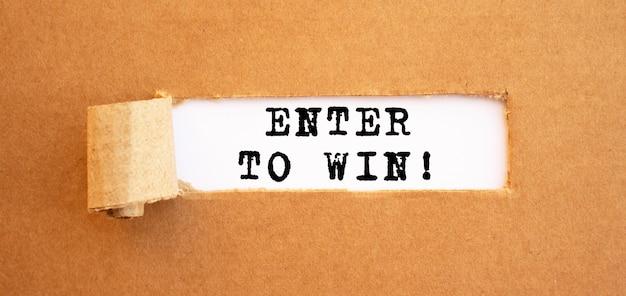 찢어진 갈색 종이 뒤에 나타나는 enter to win 텍스트. 디자인, 개념.