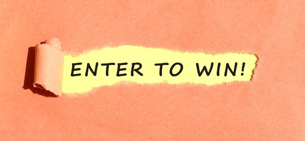 The text enter to win appearing on yellow paper behind torn color paper top view