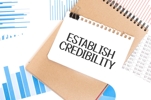 Text establish credibility on white paper sheet and brown paper notepad on the table with diagram. business concept