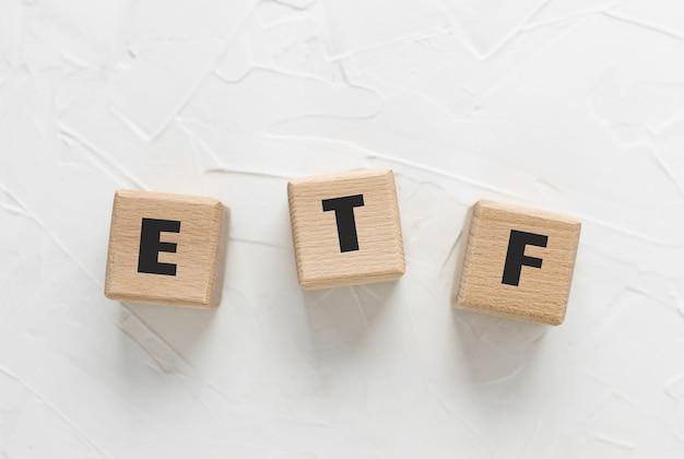 Текст etf на деревянных кубиках на белом текстурированном фоне замазки. аббревиатура от «exchange traded funds». квадратные деревянные блоки. вид сверху, плоская планировка.