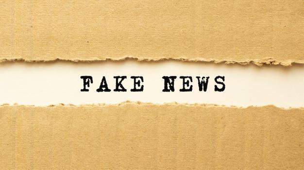찢어진 갈색 종이 뒤에 나타나는 fake news 텍스트. 평면도.