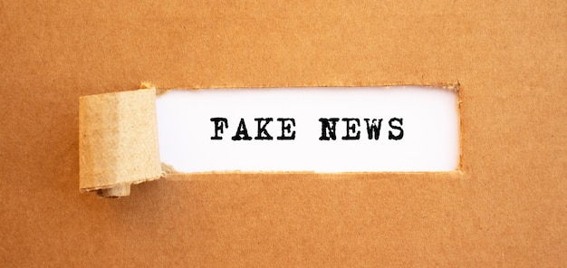 破れた茶色の紙の後ろに現れるテキストフェイクニュース